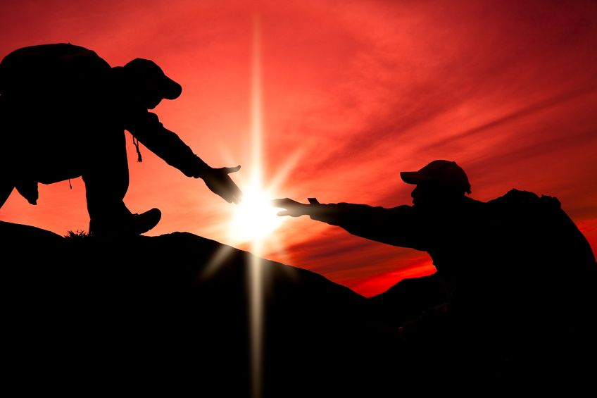14522778 - silhouette of helping hand between two climber