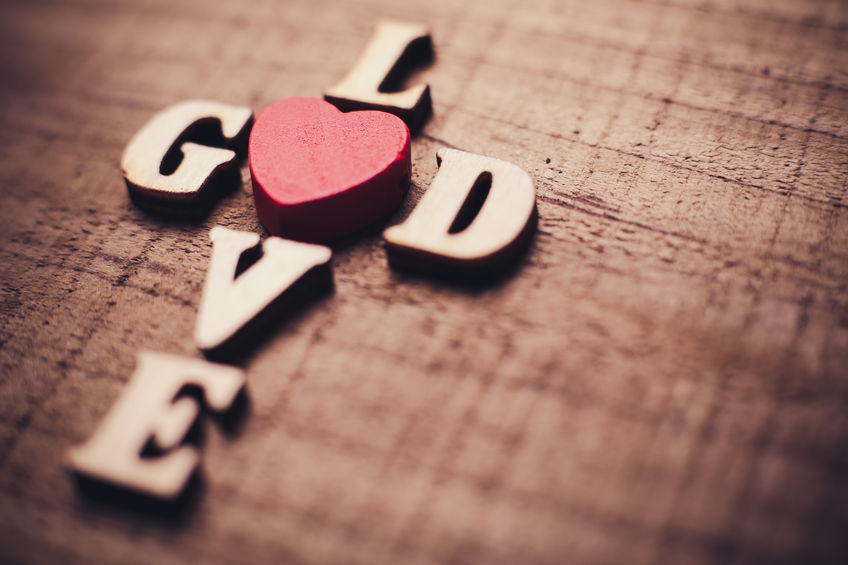 46602455 - god is love concept text lying on the rustic wooden background.