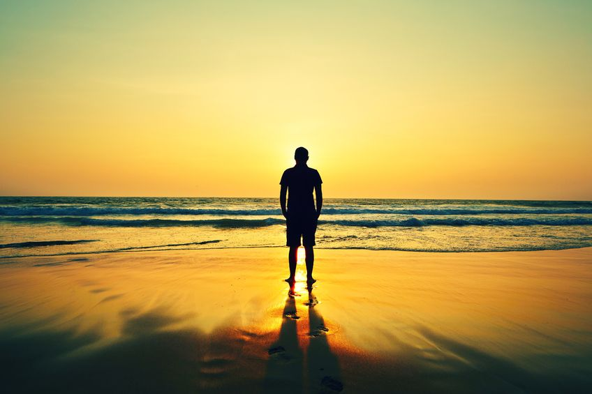 24367848 - silhouette of young man on the beach at sunset.