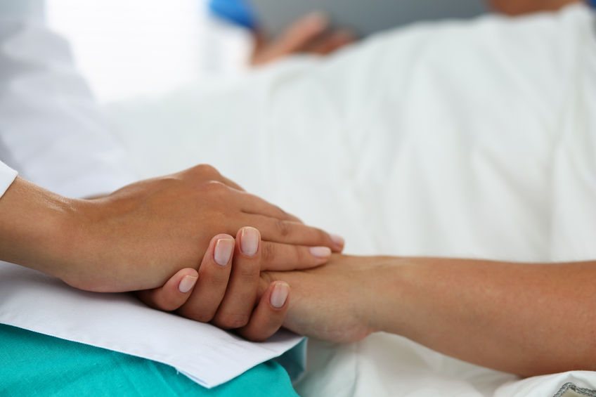 47107480 - friendly female doctor hands holding patient hand lying in bed for encouragement